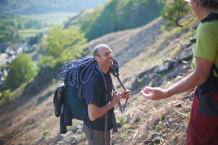 Rock climbers on hillside chatting and smiling LANG_EVOIMAGES