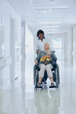 Hospital Orderly Pushing Senior Female Patient In Wheelchair Stock