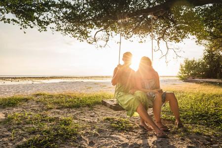 Two women sitting on beach tree swing at sunset, Gili Trawangan, Lombok, Indonesia LANG_EVOIMAGES