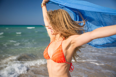 Woman holding up scarf on beach