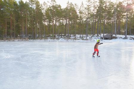 Boy ice skating on frozen lake, Gavle, Sweden LANG_EVOIMAGES