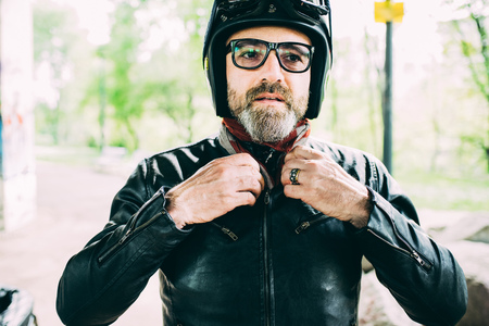 54: Mature male motorcyclist wearing eyeglasses fastening leather jacket