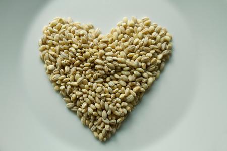 Barley grain in heart shape on plate