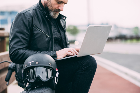 54: Mature male motorcyclist on roadside using laptop LANG_EVOIMAGES