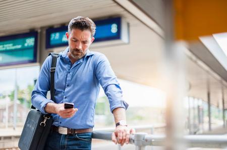 one mature man only: Mature businessman reading smartphone text on railway platform