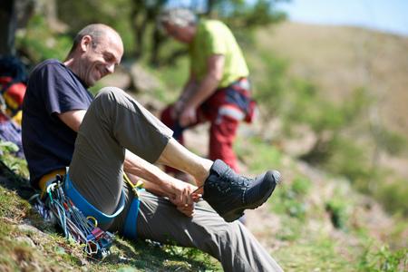 cumbria: Man sitting on hillside putting on hiking boot smiling