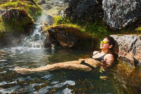 Woman wearing bikini relaxing in geothermal spa, Landmannalaugar, Fjallabak, Iceland LANG_EVOIMAGES