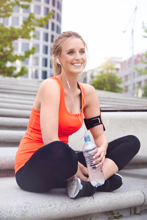 spandex: Woman sitting cross legged holding water bottle looking at camera smiling LANG_EVOIMAGES