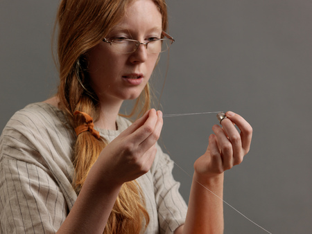 threading hair: Young female designer threading a sewing needle