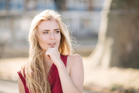 Portrait of pretty young woman with long blond hair in park