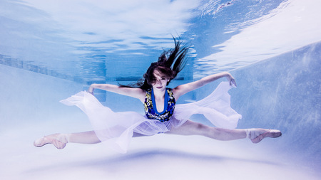 out of context: Underwater view of teenage girl, wearing ballet shoes, in dance position