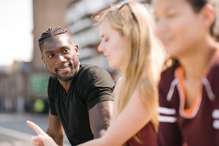 brixton: Three adult friends talking in skatepark LANG_EVOIMAGES