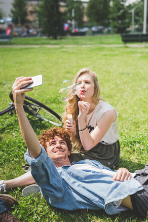 Couple taking selfie in park LANG_EVOIMAGES