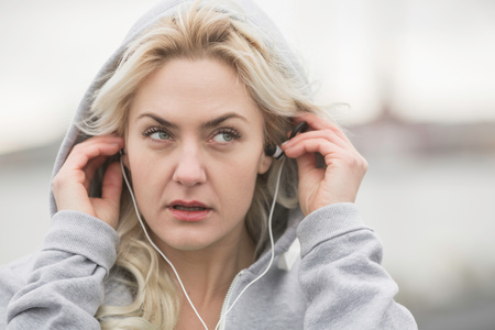 Female runner putting in earphones on dockside