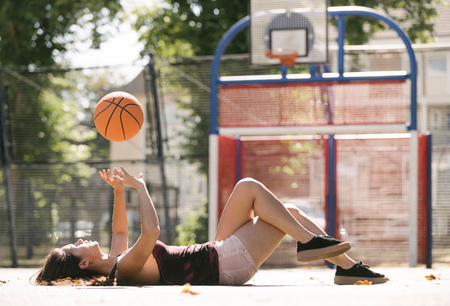 brixton: Young woman lying on basketball court throwing ball LANG_EVOIMAGES