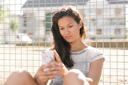 brixton: Woman reading smartphone updates by wire fence LANG_EVOIMAGES