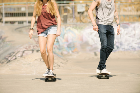 brixton: Neck down view of female and male skateboarders skateboarding in skatepark