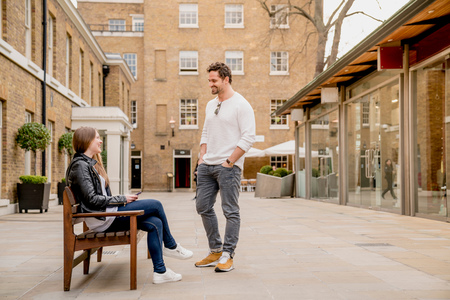 Young man greeting girlfriend sitting on bench, Kings Road, London, UK