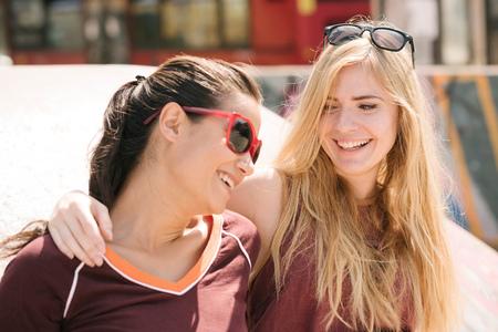 brixton: Two female skateboarding friends laughing in skatepark