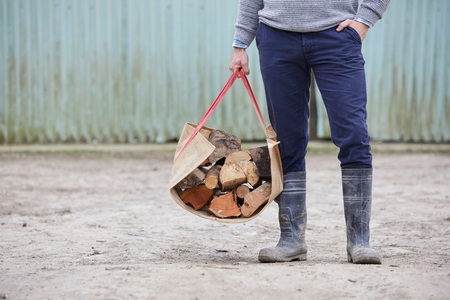 waist down: Waist down of man holding logs in log carrier LANG_EVOIMAGES