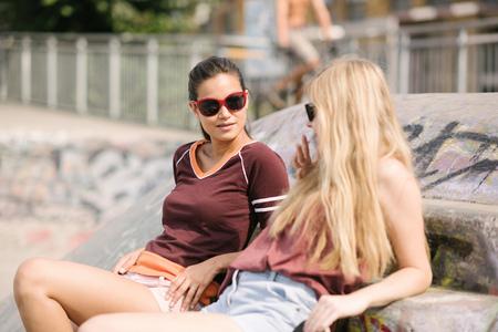 brixton: Two female skateboarding friends chatting in skatepark LANG_EVOIMAGES