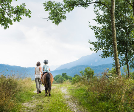 Rear view of mother guiding son riding horse, Fuessen, Bavaria, Germany
