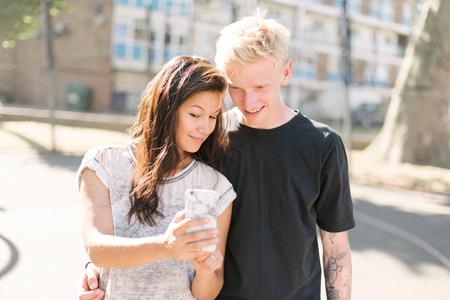 brixton: Woman and boyfriend reading smartphone update on basketball court