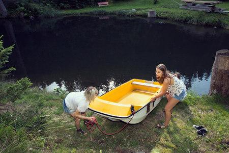 Two female friends manoeuvering rowing boat on lakeside, Sattelbergalm, Tirol, Austria LANG_EVOIMAGES