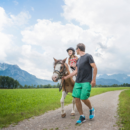 Father guiding daughter riding horse, Fuessen, Bavaria, Germany