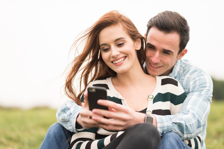 Couple sitting in field hugging looking at smartphone LANG_EVOIMAGES