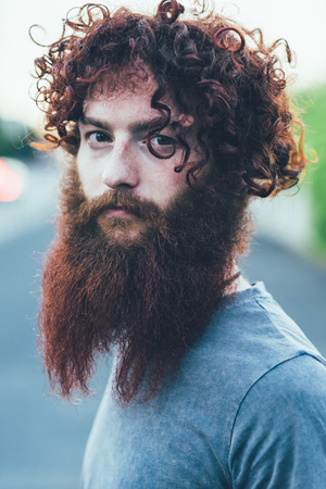 desprecio: Portrait of curly haired, bearded young male hipster LANG_EVOIMAGES