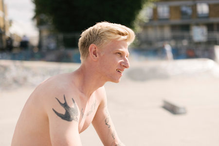 brixton: Tattooed young male skateboarder sitting in skatepark