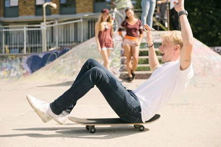 brixton: Young male skateboarder sitting on skateboard on the move in city skatepark
