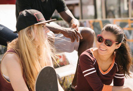 brixton: Two female friends chatting in city skatepark