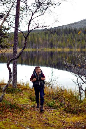 Hiker walking by lake, Kesankijarvi, Lapland, Finland