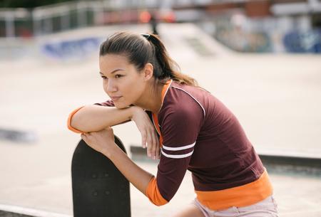 brixton: Female skateboarder in skatepark leaning on skateboard