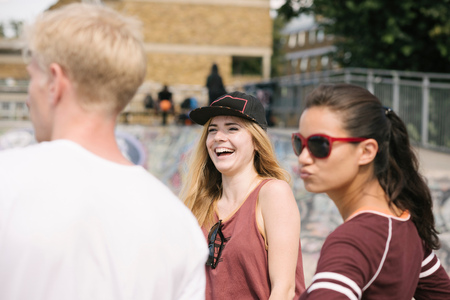brixton: Three male and female friends laughing in city skatepark