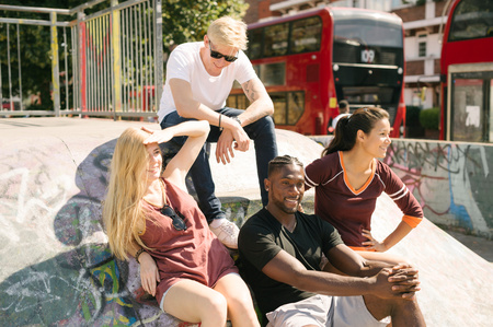 brixton: Four male and female friends sitting chatting in city skatepark