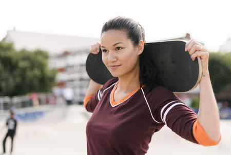 brixton: Portrait of female skateboarder carrying skateboard on shoulders
