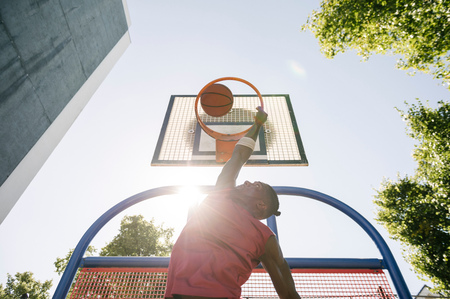 brixton: Young male basketball player throwing ball in sunlit basketball hoop LANG_EVOIMAGES