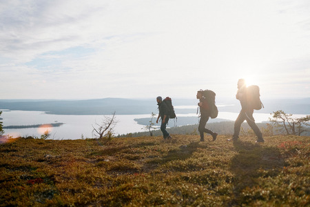 cloudscapes: Hikers crossing field by lake, Keimiotunturi, Lapland, Finland