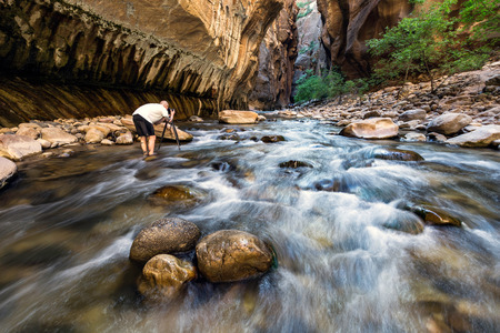 great danger: Man standing in river taking photograph, rear view, The Narrows, Zion National Park, Zion, Utah, USA