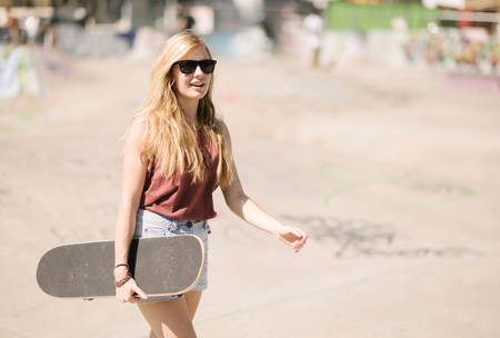 brixton: Young woman walking with skateboard in skatepark LANG_EVOIMAGES