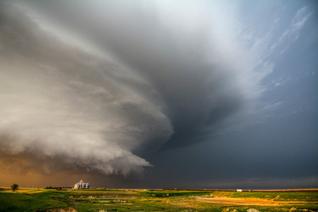 Ein Tornado-produzierendes supercell Gewitter, das über Ranchland bei Sonnenuntergang nahe Leoti, Kansas spinnt