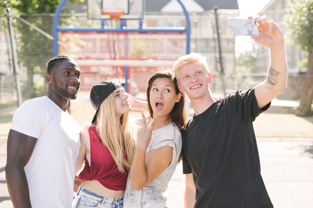 brixton: Four adult friends posing for smartphone selfie on basketball court