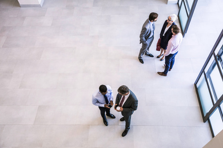 50 54 years: High angle view of businesswoman and businessmen having discussions in office atrium LANG_EVOIMAGES