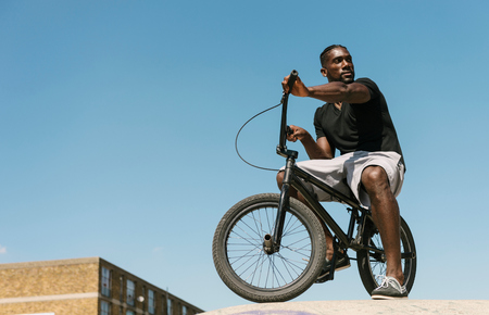 brixton: Young man on BMX bicycle looking over his shoulder in skatepark LANG_EVOIMAGES