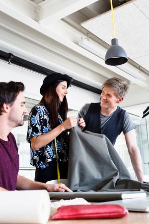 conferring: Fashion designers discussing fabric smiling
