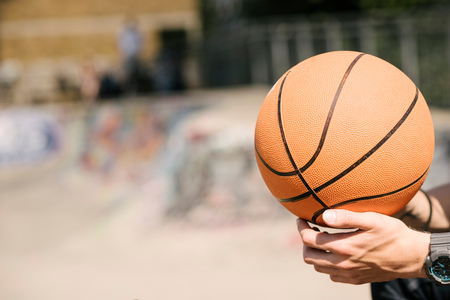 brixton: Young mans hands holding basketball ball in city skatepark