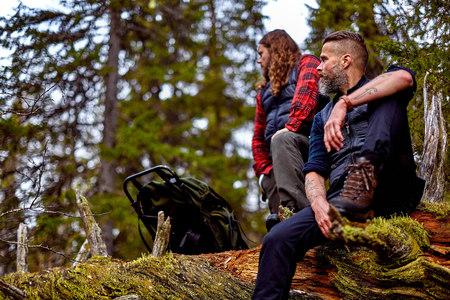 Hikers resting on fallen tree, Sarkitunturi, Lapland, Finland LANG_EVOIMAGES